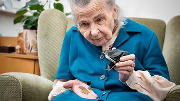 Seniorin zählt Münzen